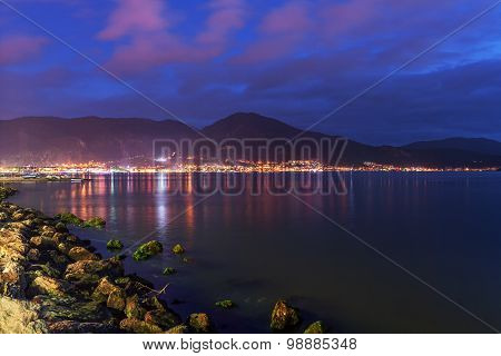 Evening on the sea on the backdrop of the mountains and city lights