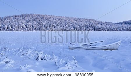 Snowy landscape and an abandoned boat.