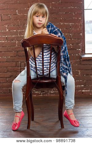 Girl  In Jeans And Shirt Thrown Sits On A Chair
