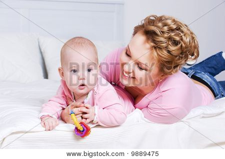 Attactive Mother Lying With Her Baby On The Bed