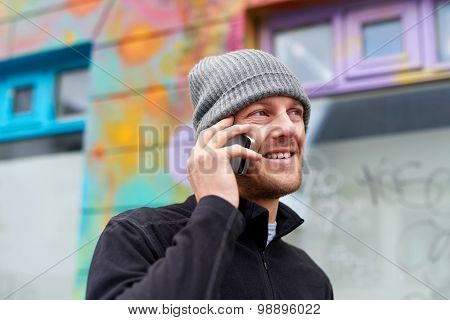 young happy caucasian adult man wearing beanie hat talking on mobile cell phone.