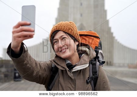 Happy travelling tourist Asian Chinese woman taking selfie in front of the Hallgrimskirkja cathedral in Reykjavik Iceland