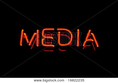 Red neon sign of the word 'Media' on a black background.
