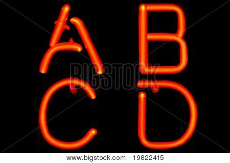 Red neon letters of the first four letters of the alphabet (ABCD).