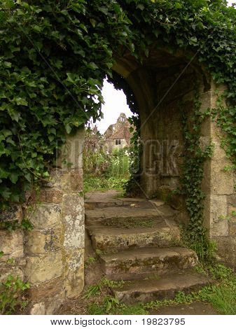Steps going up through old garden archway