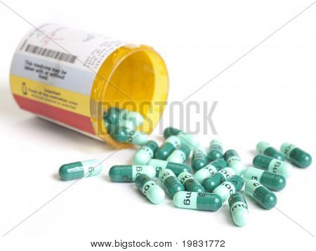 Antibiotic prescription container open with pills spilled out.