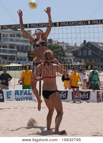 MANHATTAN BEACH, CA. - JULY 18: Jenny Kropp spiking the ball and Chelsea Hayes getting into position at the AVP Manhattan Beach Open on July 18th 2009.
