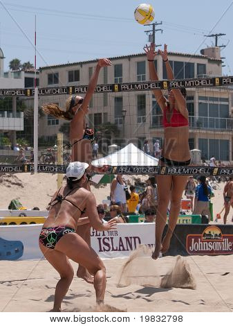 MANHATTAN BEACH, CA. - JULY 18: Jenny Kropp spiking the ball and Mariko Coverdale attempting to block with Barbra Fontana in the foreground at the AVP Manhattan Beach Open on July 18th 2009.