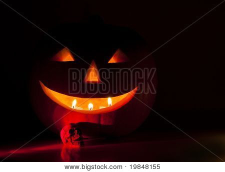 Halloween pumpkin lantern and a small skull lit in red