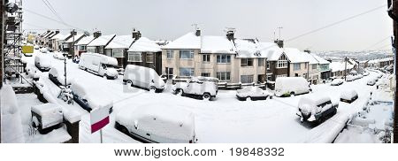 Typical english street covered by snow in winter
