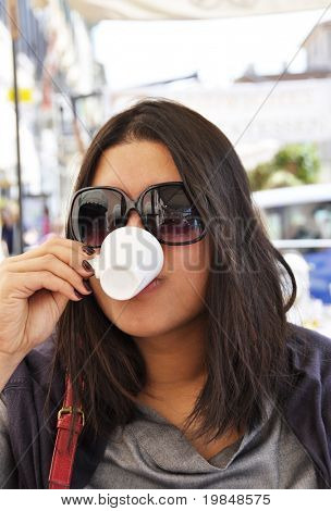 Young asian woman drinking an expresso coffee in Italy