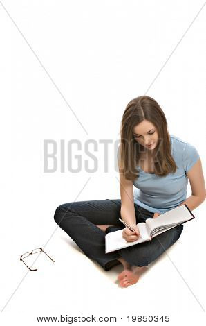 Pretty young woman seated on floor writes in a notebook