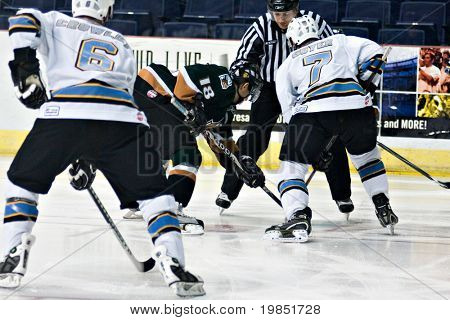 PHOENIX, AZ - DECEMBER 18: Utah Grizzlies forward James Sixsmith (#18) and Phoenix Roadrunners center Gino Guyer (#7) face off during the ECHL hockey game on December 18, 2008 in Phoenix, Arizona.