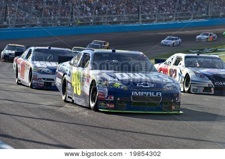 AVONDALE, AZ - APRIL 10: Jimmie Johnson (#48) leads a group of cars out of turn one at the Subway Fresh Fit 600 NASCAR Sprint Cup race on April 10, 2010 in Avondale, AZ.