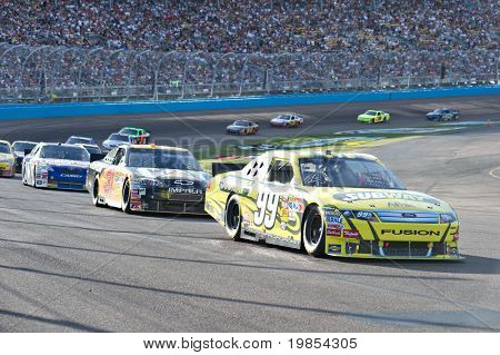 AVONDALE, AZ - APRIL 10: Carl Edwards (#99) leads a group of cars out of turn one at the Subway Fresh Fit 600 NASCAR Sprint Cup race on April 10, 2010 in Avondale, AZ.