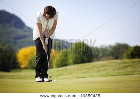 Active senior female golf player putting golf ball on green on beautiful golf course.