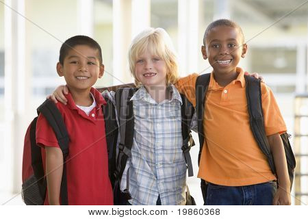 Three students outside school standing together smiling (selective focus)