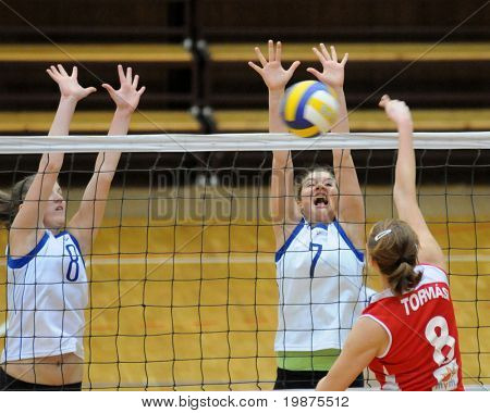 KAPOSVAR, HUNGARY - FEBRUARY 4: Timea Kondor (L) and Anna Dzunic (C) blocks the ball in the Hungarian Cup woman volleyball game Kaposvar vs Vasas, February 4, 2009 in Kaposvar, Hungary.