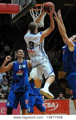 KAPOSVAR, HUNGARY - NOVEMBER 28: David Vojvoda (in white) in action at Hungarian National Championship basketball game with Kaposvar vs Debrecen on November 28, 2009 in Kaposvar, Hungary.