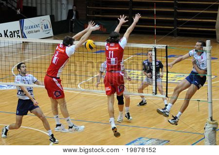KAPOSVAR, HUNGARY - DECEMBER 8: Sandor Kantor (R) strikes the ball at a CEV Cup volleyball game Kaposvar (HUN) vs Hotvolleys Wien (AUT), December 8, 2009 in Kaposvar, Hungary