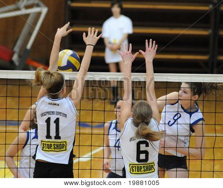 KAPOSVAR, HUNGARY - MARCH 13: Rebeka Rak (R) strikes the ball at the Hungarian NB I. League woman volleyball game Kaposvar vs Veszprem, March 13, 2010 in Kaposvar, Hungary.