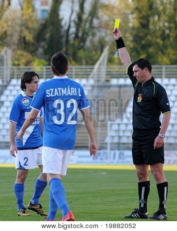 KAPOSVAR, HUNGARY - APRIL 17: Janos Takacs (referee) presents yellow card at a Hungarian National Championship soccer game Kaposvar vs MTK Budapest April 17, 2010 in Kaposvar, Hungary.