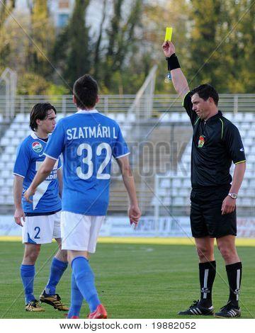 KAPOSVAR, HUNGARY - APRIL 17: Janos Takacs (referee) presents yellow card at a Hungarian National Championship soccer game Kaposvar vs MTK Budapest April 17, 2010 in Kaposvar, Hungary.