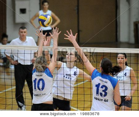 KAPOSVAR, HUNGARY - MARCH 21: Timea Kondor (C) strikes the ball at the Hungarian NB I. League woman volleyball game Kaposvar vs. Eger, March 21, 2010 in Kaposvar, Hungary.