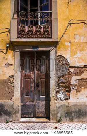 Facade of a ruined yellow house with brown door and window