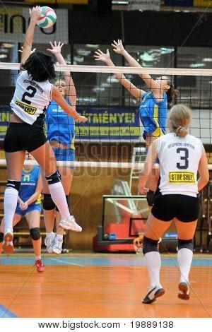 KAPOSVAR, HUNGARY - OCTOBER 10: Dora Szelle (L) strikes the ball at the Hungarian NB I. League woman volleyball game Kaposvar vs Veszprem, October 10, 2010 in Kaposvar, Hungary.