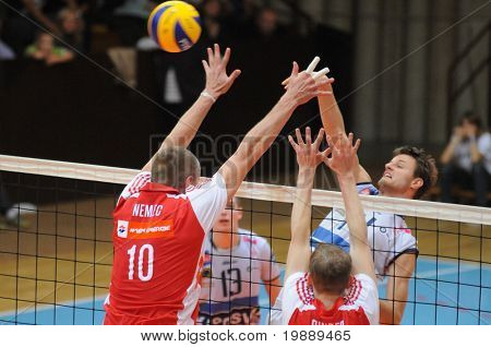 KAPOSVAR, HUNGARY - OCTOBER 15: Krisztian Csoma (R) strikes the ball at a Middle European League volleyball game Kaposvar (HUN) vs hotVolleys (AUT), October 15, 2010 in Kaposvar, Hungary