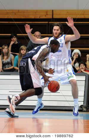 KAPOSVAR, HUNGARY - OCTOBER 24: Kurt Cunningham (in white) in action at a Hugarian Champonship basketball game Kaposvar vs. Szeged October 24, 2010 in Kaposvar, Hungary.