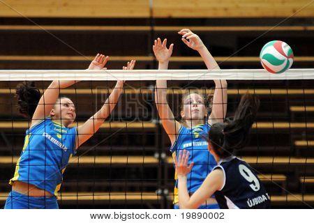KAPOSVAR, HUNGARY - OCTOBER 31: Rebeka Rak (C) blocks the ball at the Hungarian NB I. League woman volleyball game Kaposvar vs Ujbuda, October 31, 2010 in Kaposvar, Hungary.