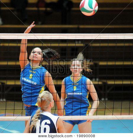 KAPOSVAR, HUNGARY - OCTOBER 31: Barbara Balajcza (L) strikes the ball at the Hungarian NB I. League woman volleyball game Kaposvar vs Ujbuda, October 31, 2010 in Kaposvar, Hungary.