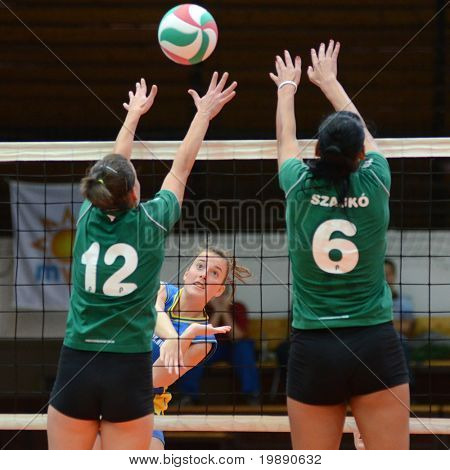 KAPOSVAR, HUNGARY - NOVEMBER 14: Zsanett Pinter (C) strikes the ball at the Hungarian NB I. League woman volleyball game Kaposvar vs Miskolc on November 14, 2010 in Kaposvar, Hungary.