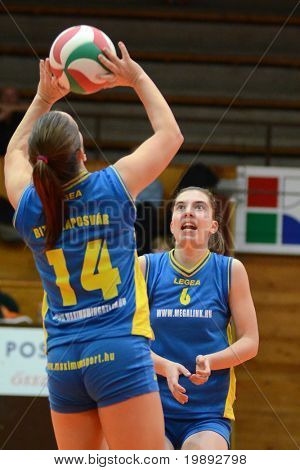 KAPOSVAR, HUNGARY - DECEMBER 19: Dora Ihasz (L) posts the ball at the Hungarian NB I. League woman volleyball game Kaposvar vs Palota Bollhoff on December 19, 2010 in Kaposvar, Hungary.