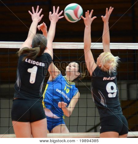 KAPOSVAR, HUNGARY - JANUARY 23: Szandra Szombathelyi (C) strikes the ball at the Hungarian NB I. League woman volleyball game Kaposvar vs Miskolc, January 23, 2011 in Kaposvar, Hungary.
