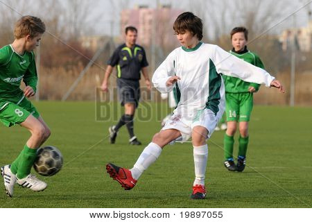 KAPOSVAR, HUNGARY - MARCH 9: Bence Bodo (in white) in action at the Hungarian National Championship under 13 game between Kaposvar and Airnergy FC on March 9, 2011 in Kaposvar, Hungary.