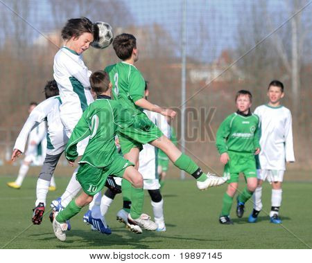 KAPOSVAR, HUNGARY - MARCH 9: Bence Szabo (in white) heads the ball at the Hungarian National Championship under 13 game between Kaposvar and Airnergy FC on March 9, 2011 in Kaposvar, Hungary.