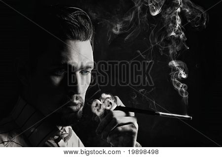 Studio Portrait Of A Young Man Smoking A Cigarette