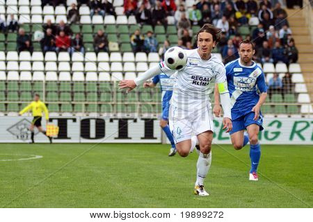 KAPOSVAR, HUNGARY - APRIL 16: Lorant Olah (in white) in action at a Hungarian National Championship soccer game - Kaposvar vs MTK Budapest on April 16, 2011 in Kaposvar, Hungary.