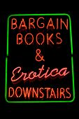 Green, red and pink neon sign of the words 'Bargain books & erotica downstairs'.