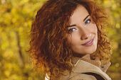 Romantic dreamy girl with beautiful red hair walks in autumn park. The mood of autumn, leaf fall. Au poster
