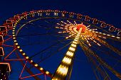 Ferris Wheel In The Evening. Cabins Of A Ferris Wheel Illuminated With Colored Lamps. Rides At City poster