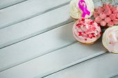 High angle view of Breast Cancer Awareness pink ribbons on cupcakes over white wooden table poster