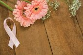 Close-up of pink Breast Cancer Awareness ribbon by gerbera flowers on wooden table poster