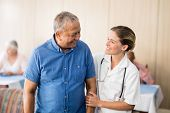Smiling senior man looking at young female doctor at retirement home poster