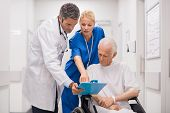 Doctor and nurse with senior patient in wheelchair at hospital corridor talking. Mature doctor showi poster