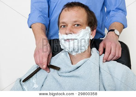 Man, sitting in a barber shop, looking into the camera whilst being shaven by the barber