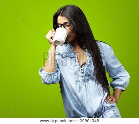 portrait of a pretty young woman drinking coffee on a cup against a green background